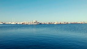 View over the still waters of Fremantle Fishing Boat Harbour, near Perth, Western Australia, on a calm morning in winter, with rows of yachts and boats berthed in the background.