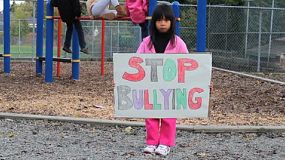 A little Asian girl carries a home made sign that she made to try to stop bullying at her local school.