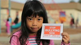"A cute little Asian girl holds up a ""STOP BULLYING NOW"" sign on the school playground."