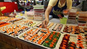 A Thai street food vendor prepares to sell fresh sushi at the market in Bangkok, Thailand.