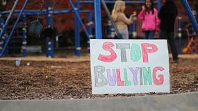 "A group of students stand behind a ""stop bullying"" sign on the school playground serving as a reminder for everyone."