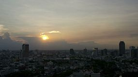 View across Bangkok, Thailand as the sun sets behind brewing storm clouds. 4k and 1080p timelapse.