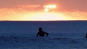 A Surfer waiting for a wave and catching a small wave at South Cottesloe Beach in Western Australia, with a fiery sunset in the background.