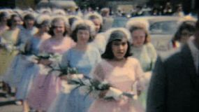 A group of pretty teenage girls pass by in a Catholic graduation processional.