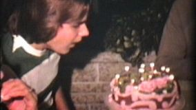 A teenage boy blows out the candles on his unusually pink birthday cake.