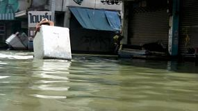 A young Thai man pushes a styrofoam container down a flooded street during the floods in Bangkok, Thailand.