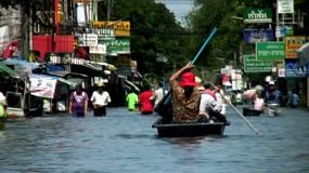 Thai people do their best to navigate the flooded streets of Bangkok in boats or walking up to their waist in flood water.