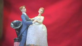 A classic shot of a toy bride and groom, prince and princess dancing around and around against a red back drop.