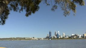 Tracking shot revealing the view of Perth City, from behind a tree, across the Swan River. Perth is the capital of Western Australia.