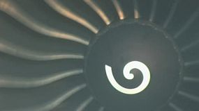 A crazy turbo jet engine spins around and around while it sits on the tarmac at the airport.