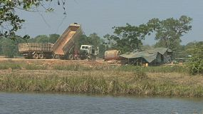 Two large dump trucks are parked at an rural construction work site in eastern Thailand.