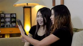 Two young asian friends playing with a tablet computer, while sitting on a sofa in their lounge room.