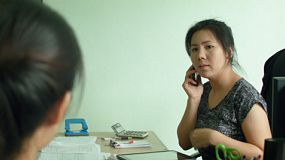Two female Asian office workers discussing a job while one talks on the phone.