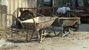A cool pan shot of a stack of palettes to some old wheelbarrows sitting at a work site in the slums of Bangkok, Thailand.