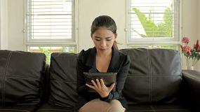 A young asian businesswoman reading and thinking on her tablet computer, while sitting on a sofa/couch.