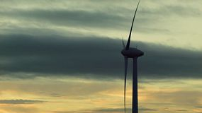 A wind turbine on a wind farm silhouetted against the cloudy dusk skies at sunset.