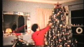 A middle aged woman takes a moment to admire the Christmas tree that she has just decorated.