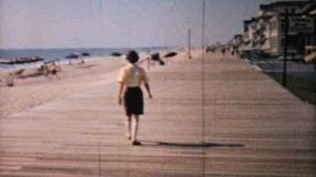 A pretty woman enjoys walking on the boardwalk near the beach in Ocean City, New Jersey while on her honeymoon in 1958.