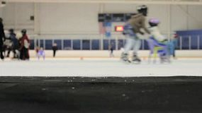 A young woman carefully walks onto the ice at the local skating rink.