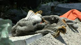 A pair of old woolen work gloves sit on a rock after a hard days work in the slums of Bangkok, Thailand.