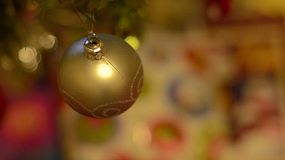A yellow bauble hanging on a christmas tree, focus racking to a wrapped present under the tree.