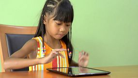 A young Asian girl walks in and sits at a table, then starts using a tablet computer.