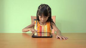A cute young Asian girl sitting at a table playing games on her iPad / tablet computer.
