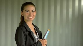 Young asian businesswoman turning and smiling at the camera, holding a pile of papers and documents.