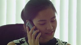 A young Asian office worker talking on the phone in her office.