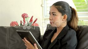 A young businesswoman thinking as she is working on her tablet computer.