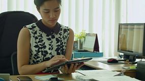 A young Asian office worker using a tablet computer and writing on a notebook while sitting at her desk.