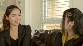 Two young asian female office workers in business attire sitting on a sofa chatting.
