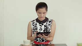 A beautiful young Asian woman relaxing at a coffee shop, using her tablet computer while drinking a cup of tea.