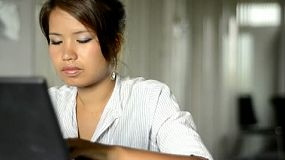 Young Asian woman typing on a laptop computer.