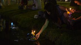 BANGKOK, THAILAND - NOVEMBER 17, 2013:  A young Thai woman releasing a krathong into a pond at night in Bangkok, Thailand.