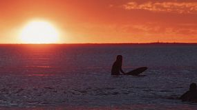 Young woman surfing at South Cottesloe Beach in Western Australia, as the sun sets beautifully in the background.