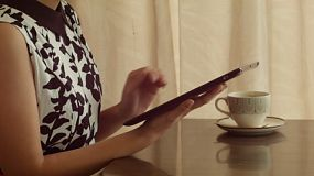 Young Asian woman playing on an iPad while drinking tea at a cafe.