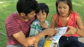 Asian Family Having Fun In The Park Reading