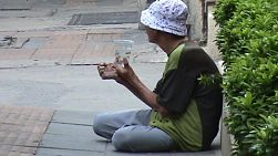 A beggar wearing a hat on the streets of Bangkok, Thailand.