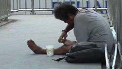 A homeless man on the streets of Bangkok, Thailand picks the sores on his feet while begging.