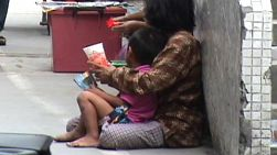 A mother and her son begging on the streets of Bangkok, Thailand.