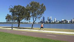 Woman exercising along the swan river, with perth city in the background, as a cyclist rides past.
