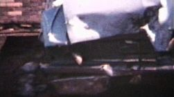 A slow pan of a wrecked car from 1962. (Vintage 8mm film)
