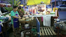 A Thai street food vendor making a tasty spicy soup at the market in Bangkok, Thailand.