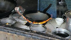 A cook adds oil to a hot wok before making a delicious Thai egg omelet in northern Thailand.