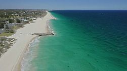 Aerial view of the sandy beach and coastline at City Beach in Perth, Western Australia on a clear windy day.