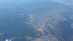 An aerial view of the city of Kelowna and Lake Okanagan flying over head.