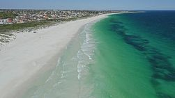 Aerial shot flying along the shore at Mullaloo Beach in Perth, Western Australia on a clear windy day.