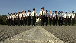 A group of air line pilots and students walk away from a plane on a runway in the shape of a V.