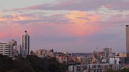 View of apartment buildings and the city next to the Perth CBD, under the colourful clouds after the sun has set.
